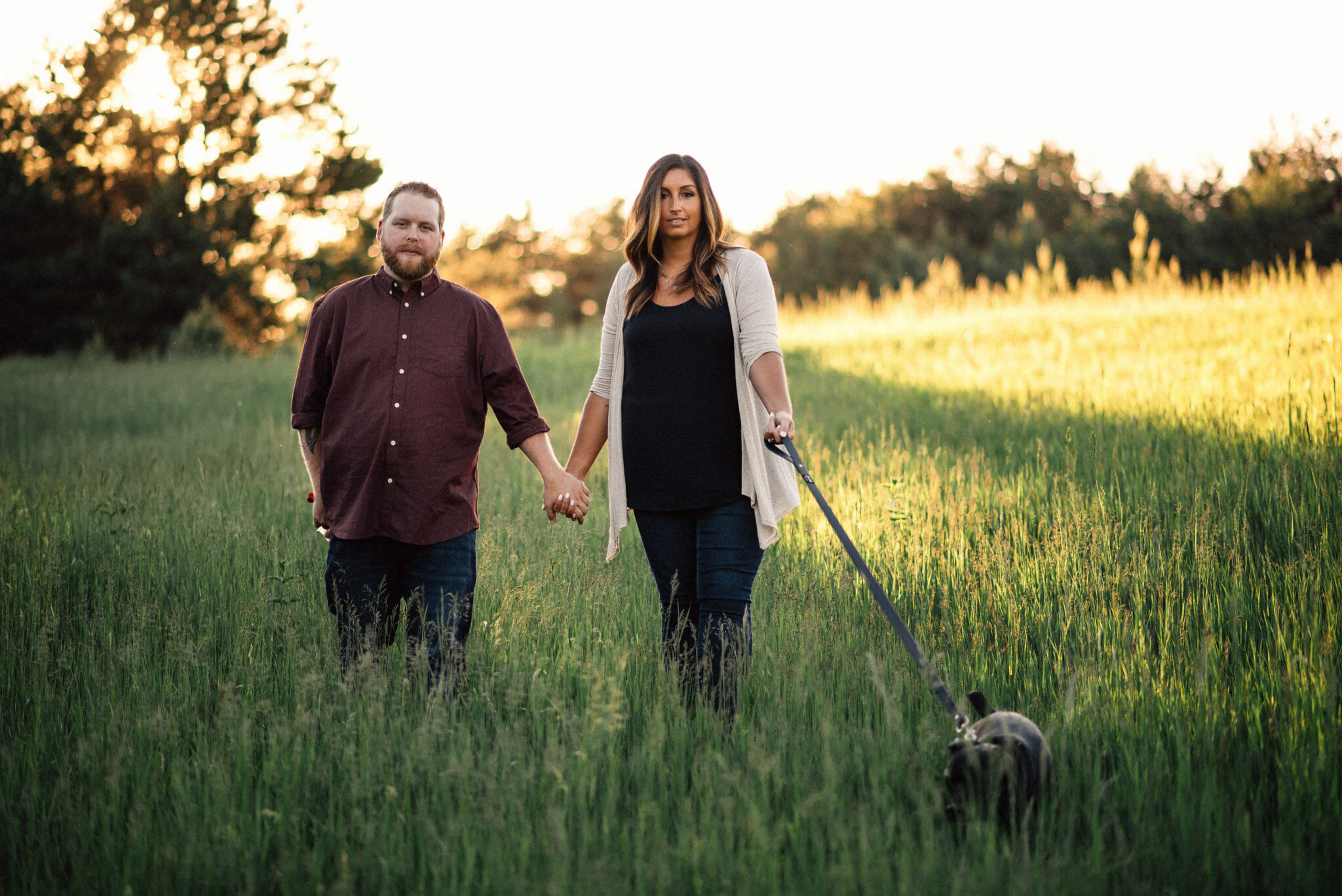 engaged couple walking in tall grass with dog during bowmanville engagement photos