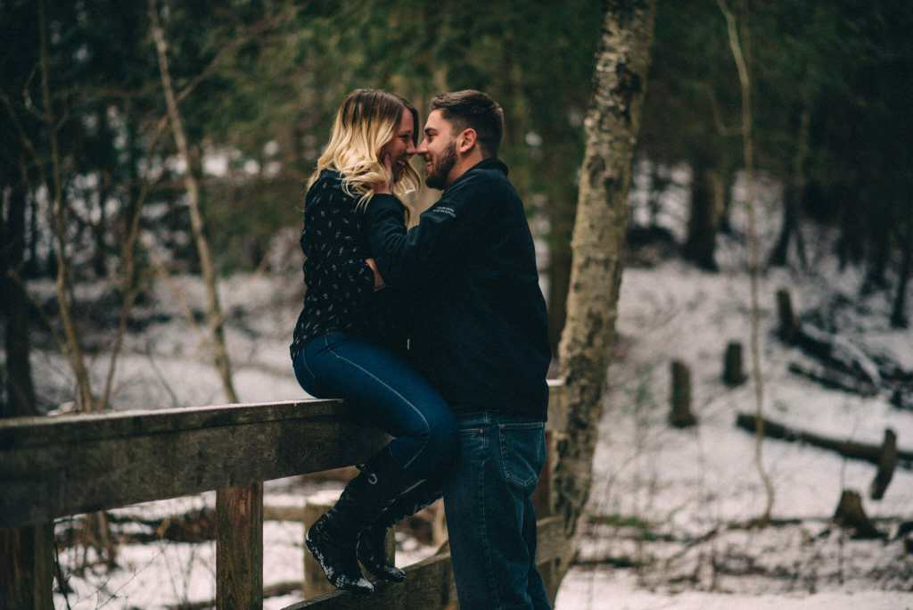 girl sits on railing held by boyfriend