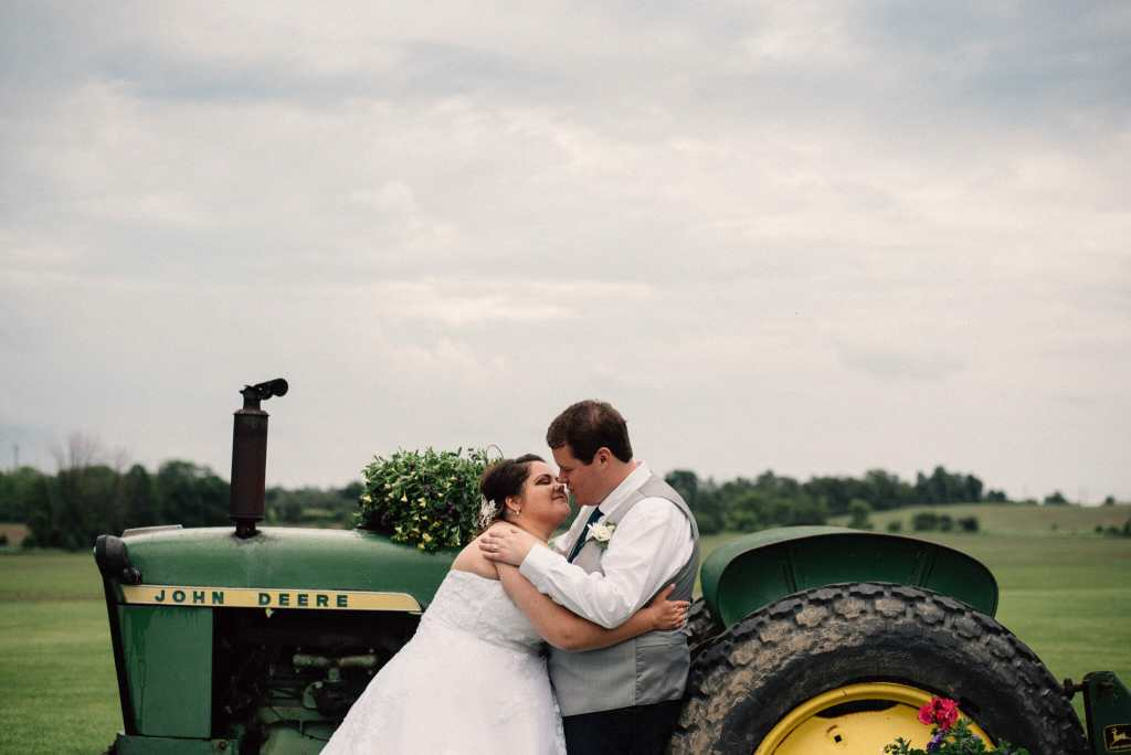 country wedding photos in front of farm tractor