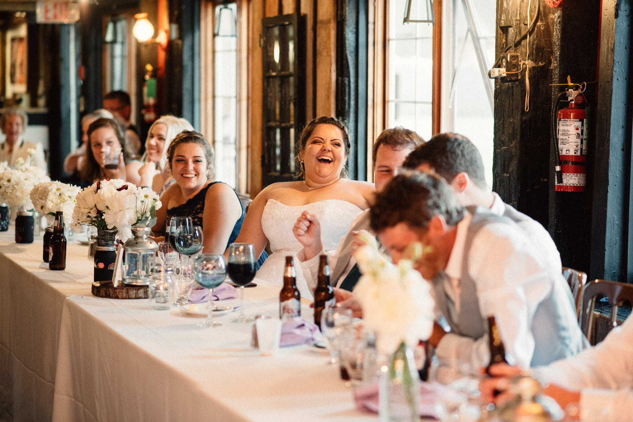 wedding party laugh during reception dinner