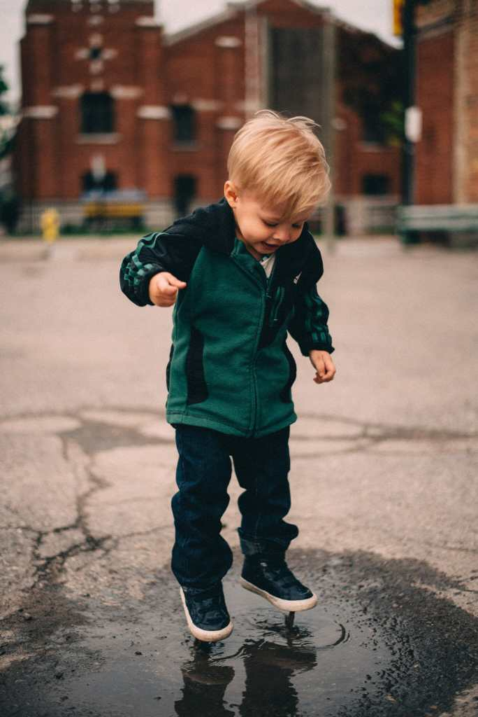 child jumps in puddle downtown oshawa