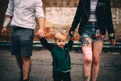 little kid walks with tattooed parents oshawa