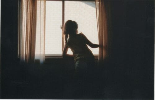 film photo of young girl in window