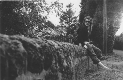 film photo of girl on mossy scottish stone wall