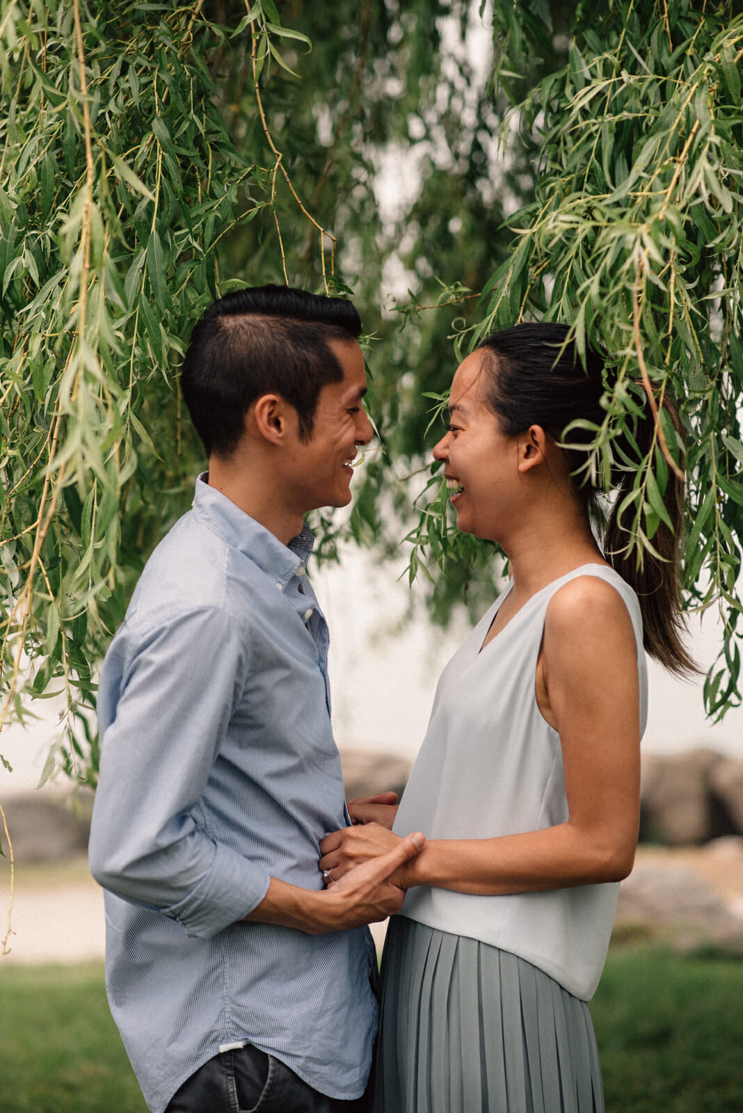 couple laugh standing under a willow tree