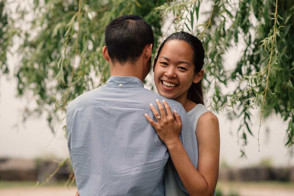 newly engaged women smiles while hugging fiance