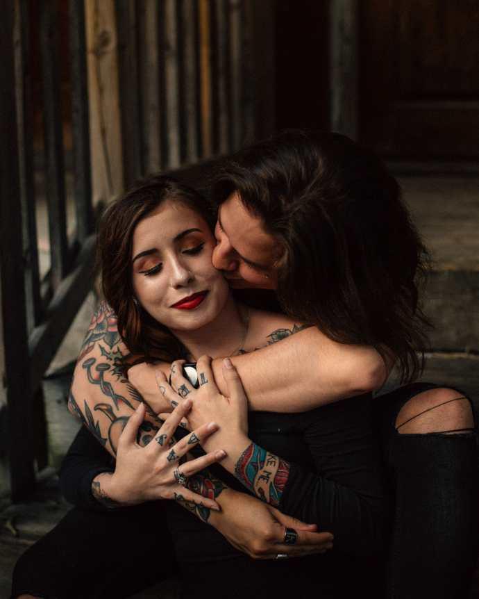 boyfriend kisses girlfriend on cheek during couple session