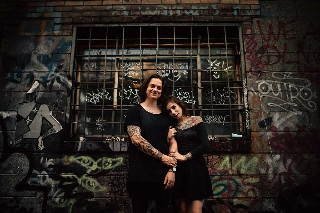 couple snuggle up for photo in graffiti alley toronto