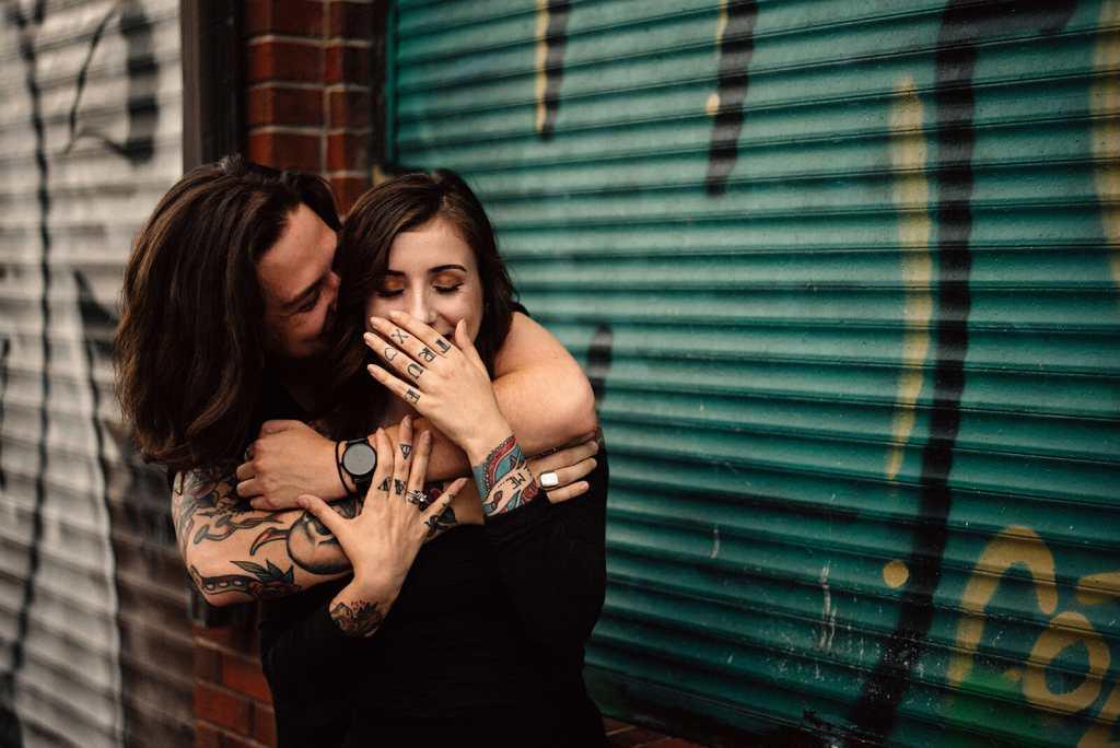 girl laughs as boyfriend whispers in her ear