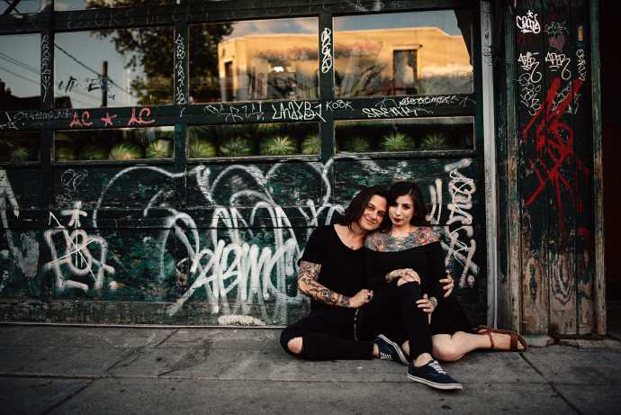 couple sits on ground in front of door with graffiti