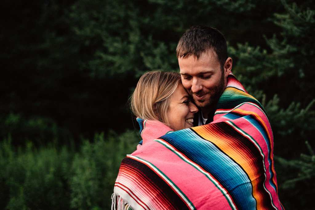 engaged couple cuddles under blanket during photo session