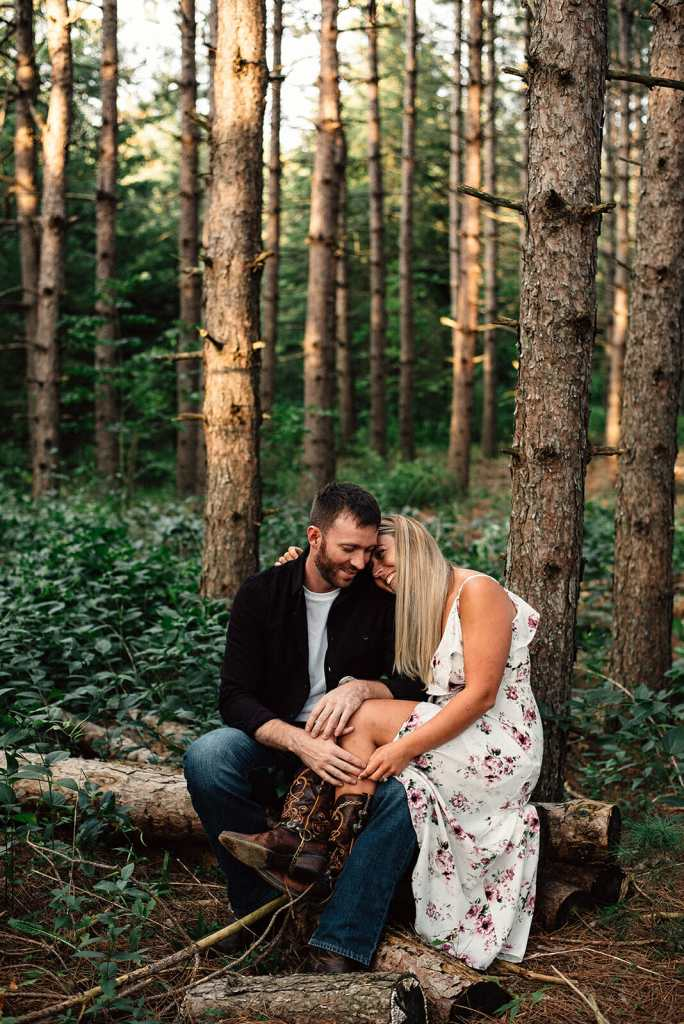 couple embraces in forest while sitting on log