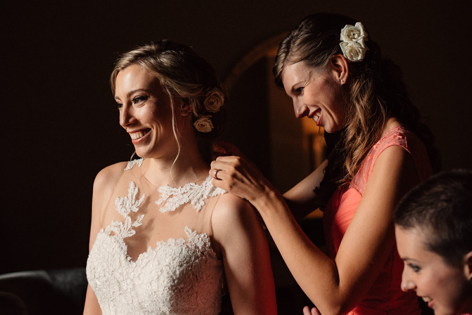 sister helps bride button up her wedding dress