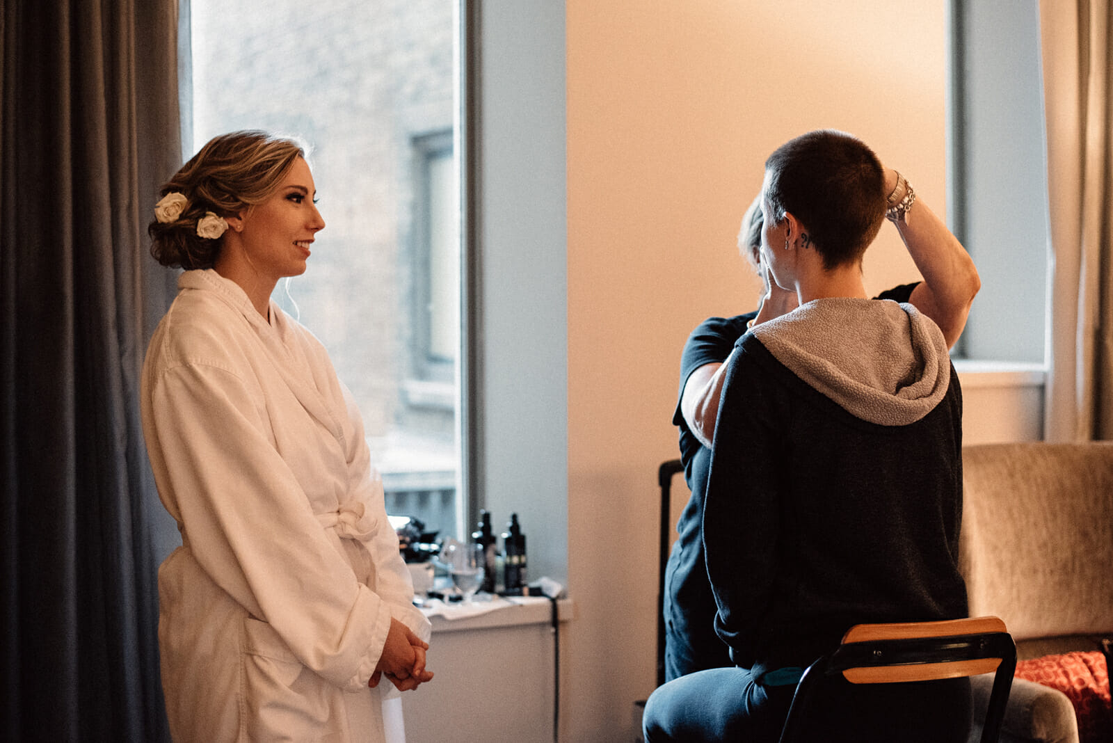 bride watches as bridesmaid gets make up done