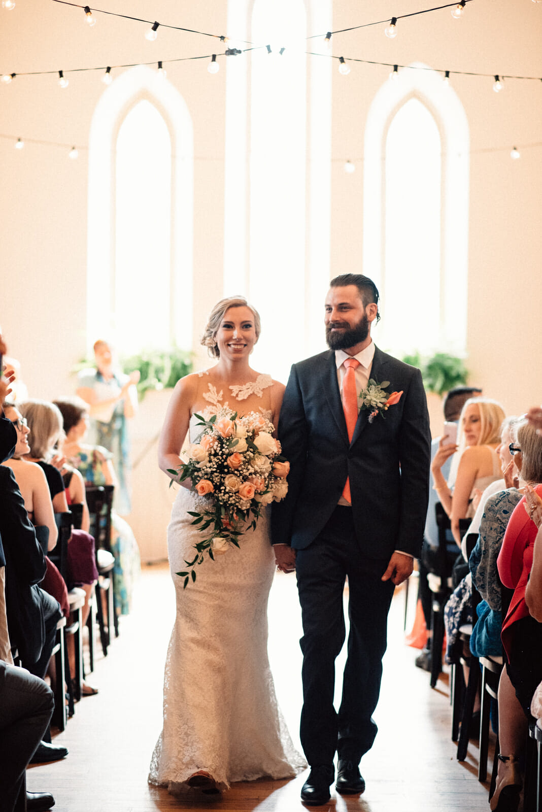 bride and groom walk down the aisle together after toronto wedding