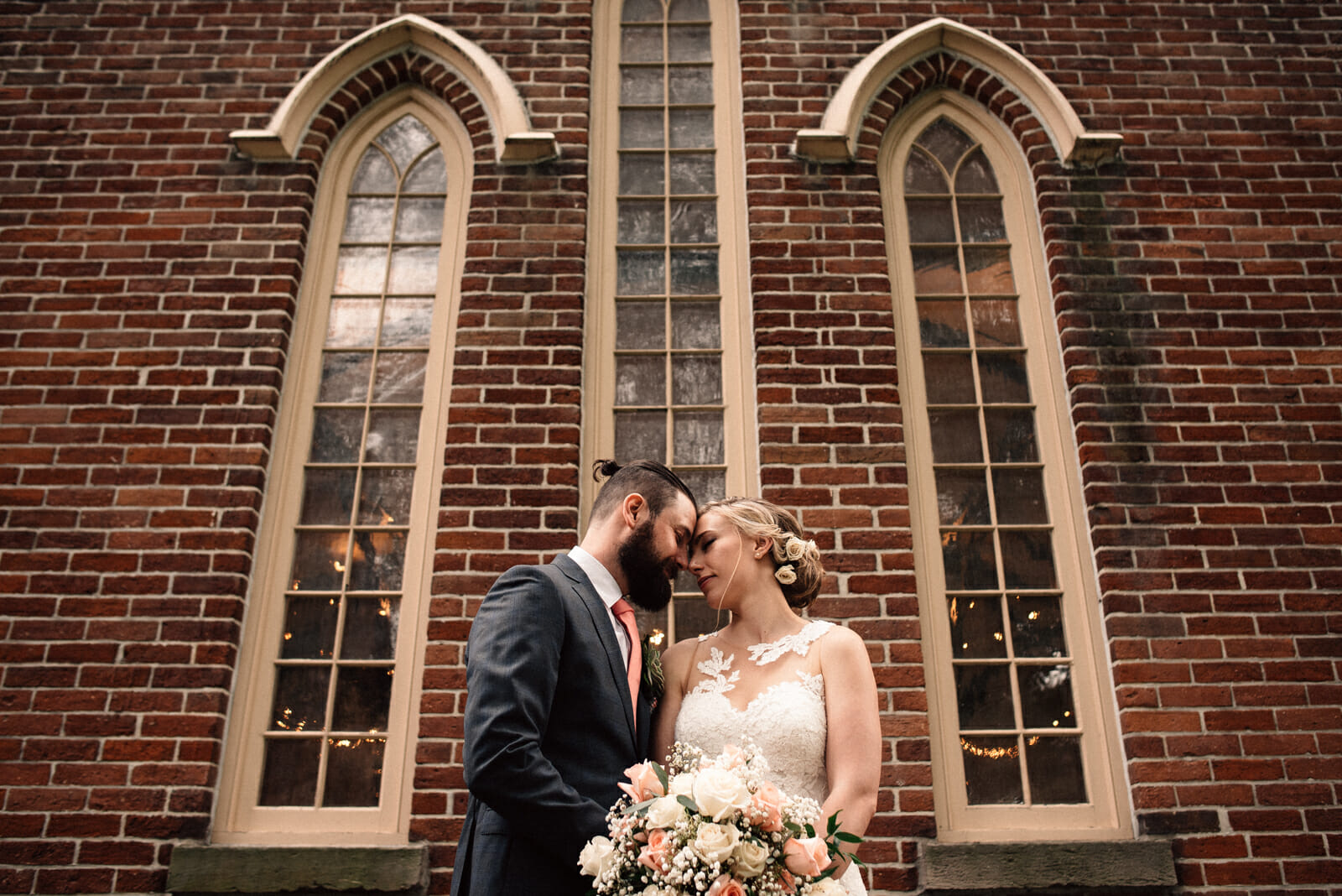 wedding photo of bride and groom in front of gothic windows