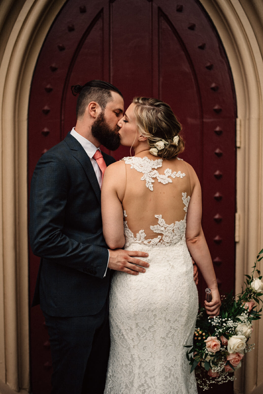 bride and groom kiss during wedding photos in front of red church door