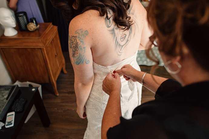 mother of bride doing up wedding dress