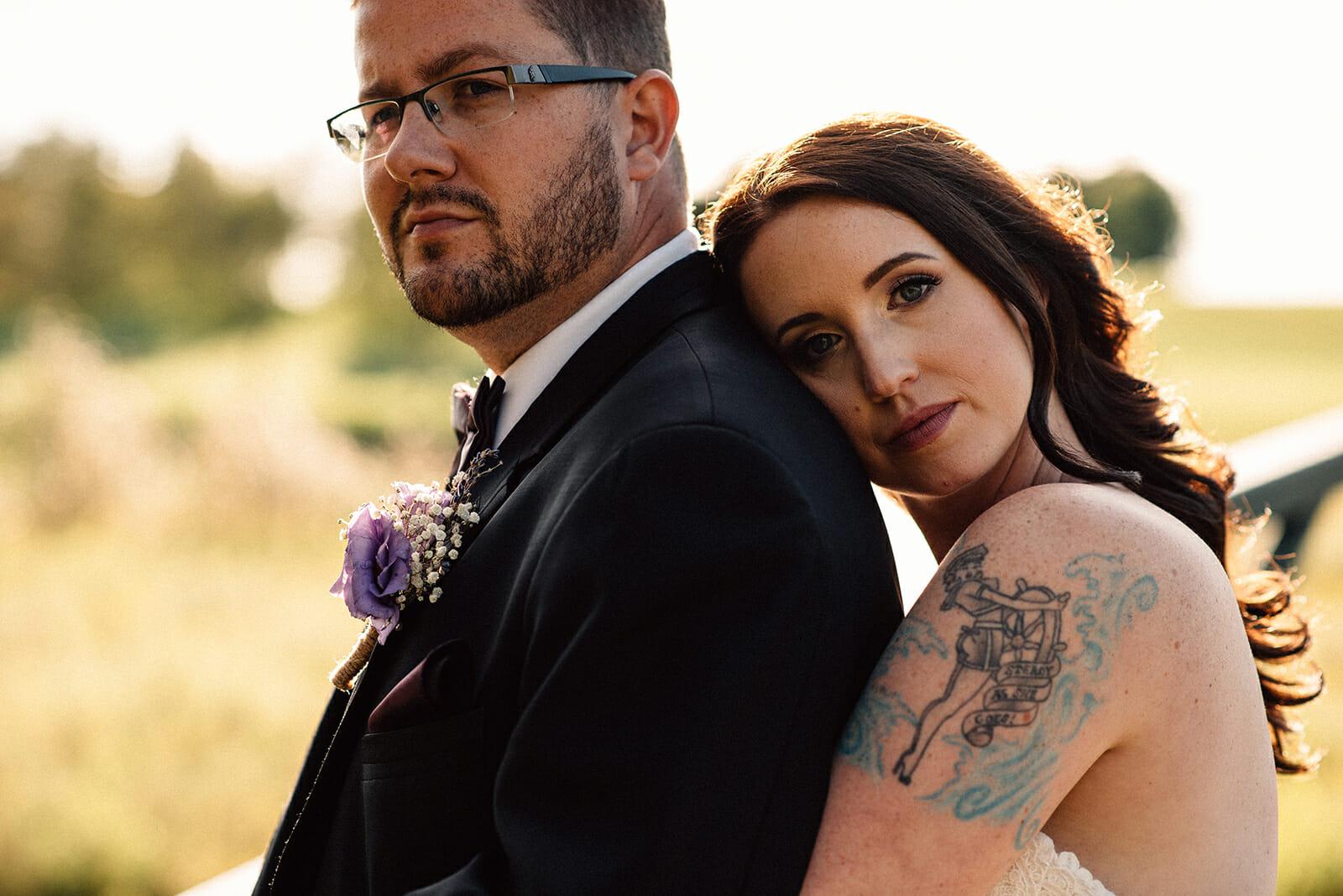 bride cuddles groom from behind