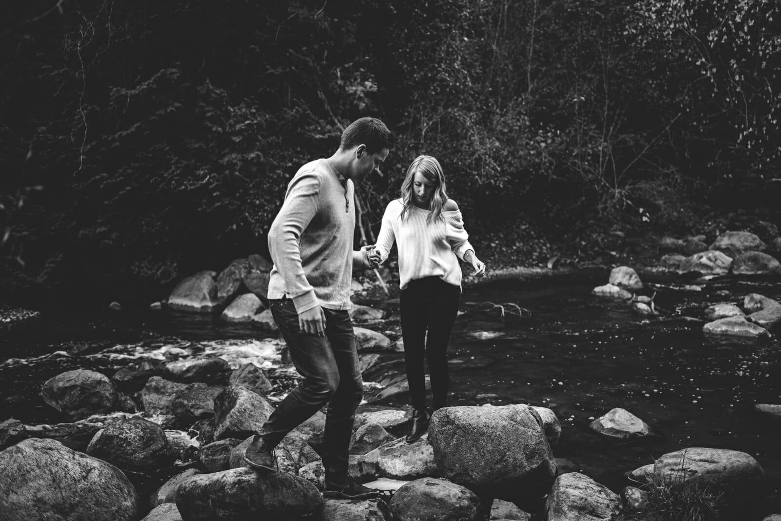 boyfriend helps his girlfriend cross river rocks