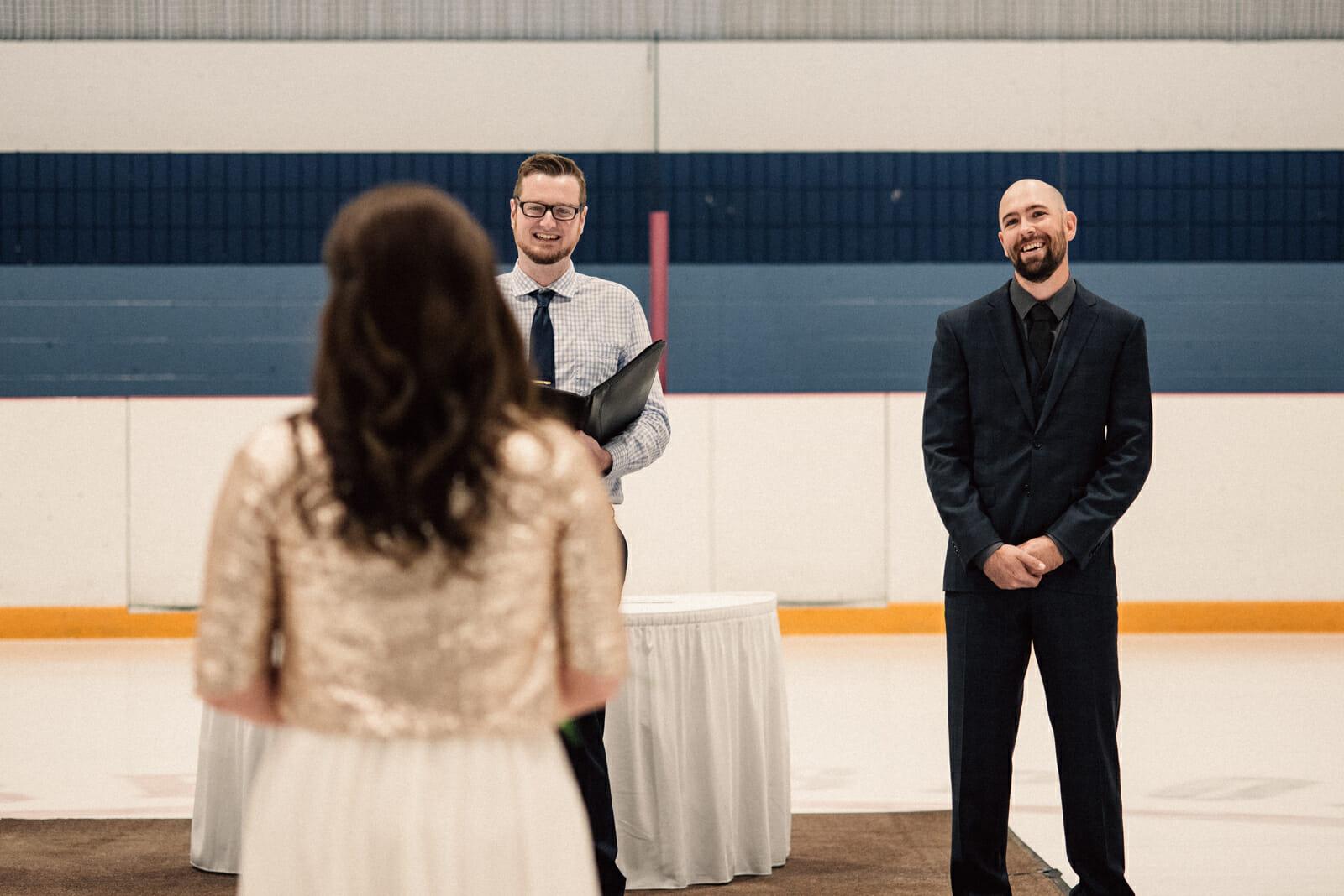 groom smiles at bride walking down aisle
