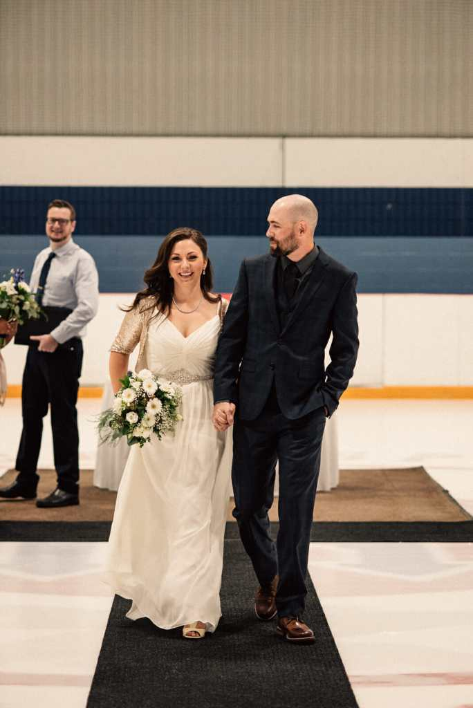 newlyweds walk down aisle on centre ice