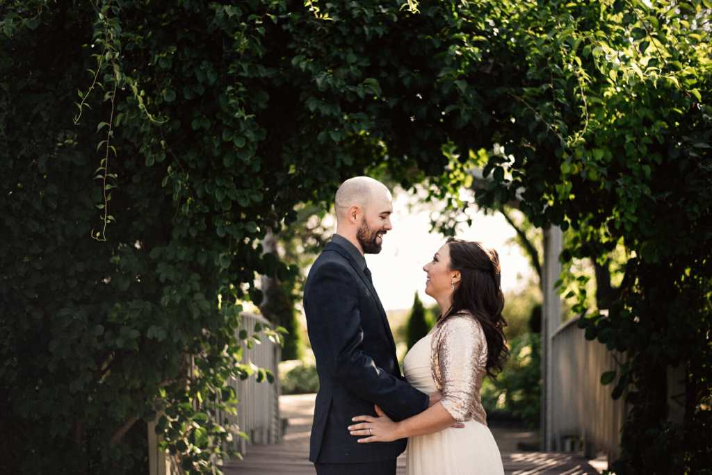 bride and groom smile under greenery arch