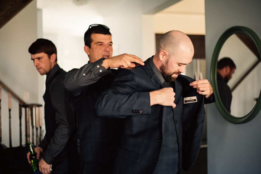 groomsmen helps groom get ready on wedding day