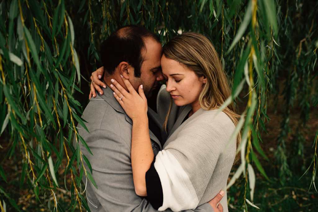 engaged couple cuddle under willow tree
