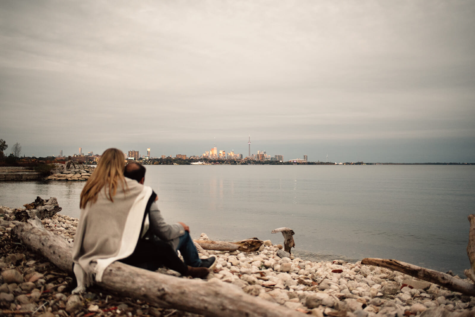 newly engaged couple looks out over lake ontario at toronto skyline