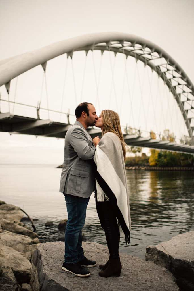 engaged couple kiss in front of the humber bay arch bridge