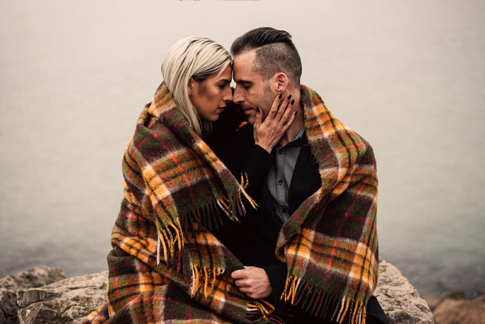 couple snuggles under blanket during fall engagement photos