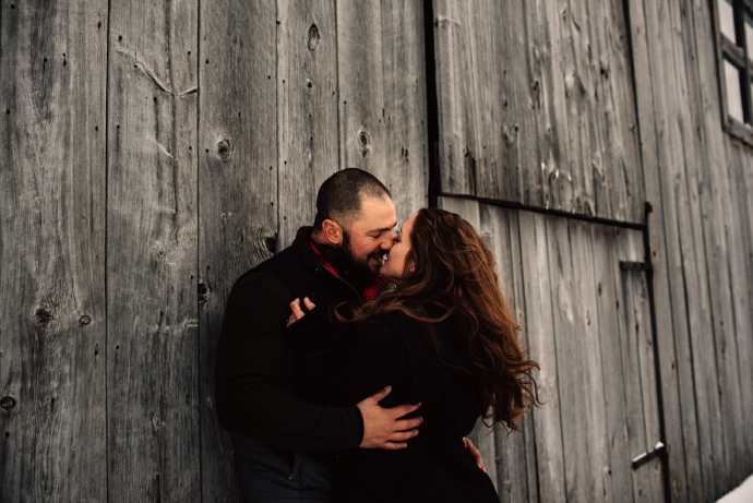 engaged couple kisses while leaning against barn