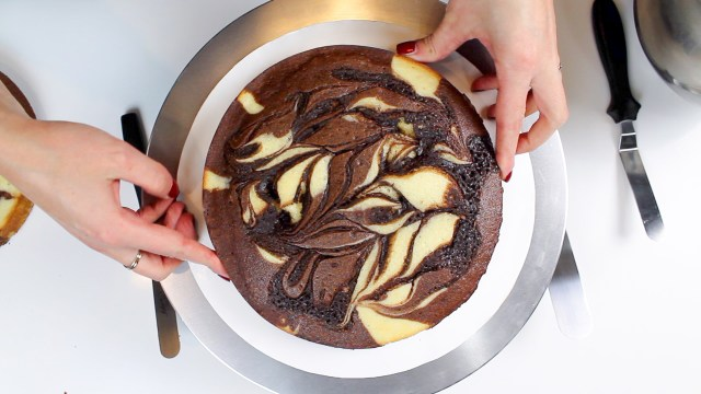 placing baked cake layer on cake board