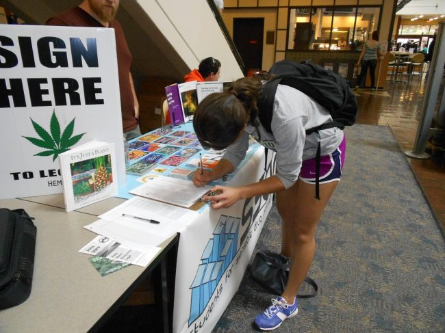 Transfer student Morgan McQuade signs the petition to legalize marijuana.
