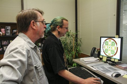 Arnold Goth (left) and Octavian Dum, two of Chemeketa's computer technicians, stare at the computer screen while waiting for the computer to finish booting up.