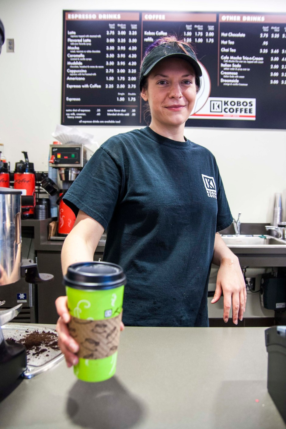 A coffee barista hands a customer a cup of java during a busy morning in Bldg. 8.