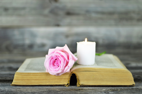 Sympathy card with burning candle and rose on open book