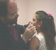 Photo of Chiropractor, Dr Cherubino treating a child with red laser light therapy
