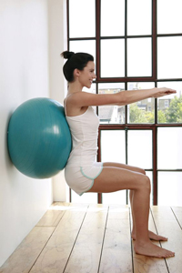 Woman dressed in white exercising with a teal blue exercise ball performing active care at home