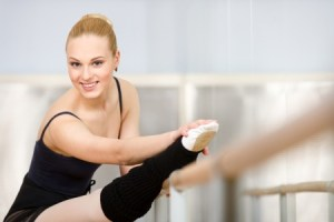 Ballerina in black leotard at the barre