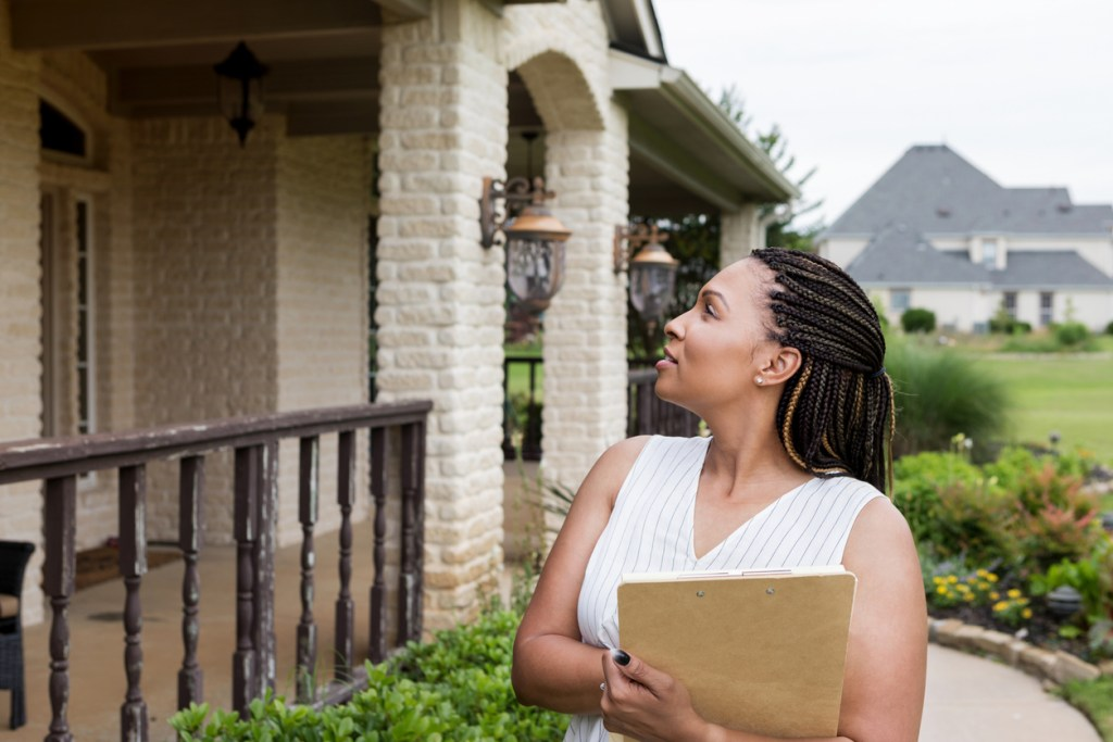 A home inspector holding a notepad with seller disclosures is looking over her shoulder at a property for sale.