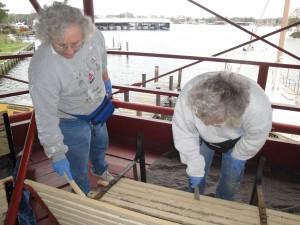 Paula and Lauren scraping the wood