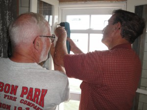 Photo By Anne Puppa Al and Robert attach interior shutter to window.