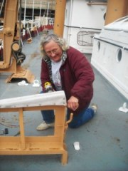 Lauren Liebrecht drilling hole in life boat davit.