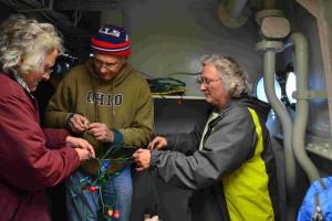 Lauren, Tony, and Paula untangle and test the lights.