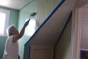 Susie painting upstairs windows.