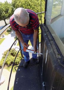 Hobie caulks gaps in siding.