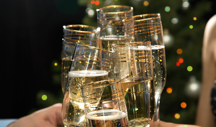 Several champagne flutes clinking together against a glitter backdrop.