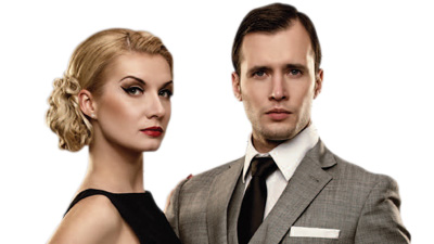 A man in a smart grey suit and a glamorous lady in black dress stand against a white backdrop.